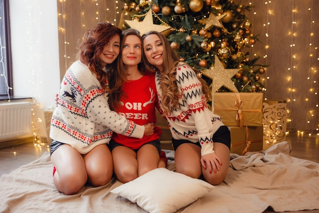Tre belle ragazze alla vigilia di capodanno. migliori amiche della giovane donna che celebrano il natale in casa. l'amicizia di divertimento non finisce mai il concetto. bellissime decorazioni natalizie dorate su un alto albero di natale