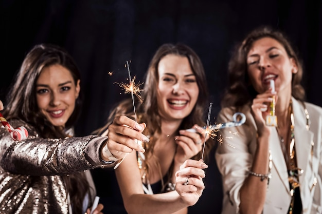 Tre belle ragazze in eleganti abiti casual si divertono con nastri e tubi e stelle filanti su uno sfondo nero in studio.
