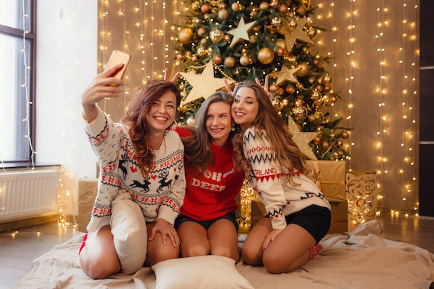 Tre belle ragazze si fanno un selfie al telefono. migliori amiche della giovane donna che celebrano il natale in casa. l'amicizia di divertimento non finisce mai il concetto. splendide decorazioni natalizie dorate su un alto albero di natale