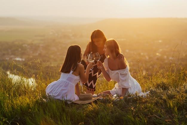 Tre belle ragazze in vacanza divertendosi, bevendo vino e mangiando frutta all'aperto sul picnic.