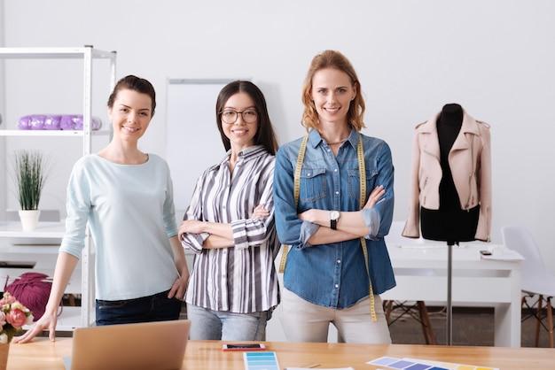 Tre belle sarte femminili piacevoli in piedi vicino al tavolo di lavoro nell'atelier e in posa per una macchina fotografica mentre sorridono