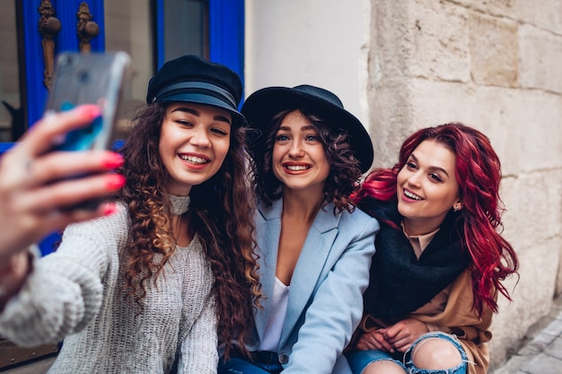 Tre belle donne che prendono selfie sulla strada della città. amici felici che si appendono e si divertono all'aperto