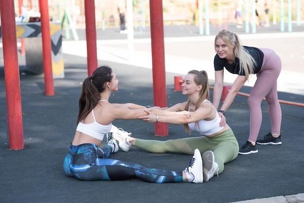 Tre ragazze belle, giovani e atletiche stanno facendo il riscaldamento sul campo sportivo in strada