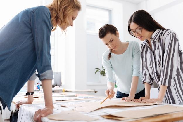 Tre belle giovani donne sarte in piedi intorno al tavolo e discutendo modelli mentre uno di loro indicava loro con una matita