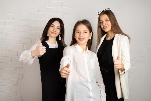 Tre belle giovani femmine con il trucco con il gesto della mano