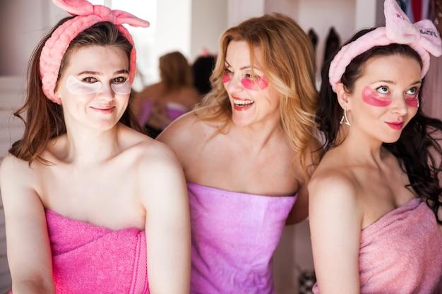 Tre belle giovani donne in asciugamani rosa, con bende cosmetiche in testa, posano per la fotocamera con macchie sotto gli occhi. .