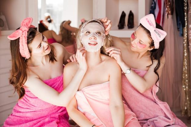 Tre belle giovani donne posano con macchie sotto gli occhi e in una maschera cosmetica in tessuto