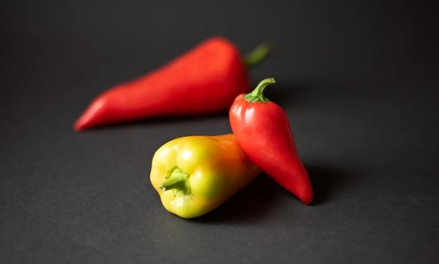 Tre peperoni su uno sfondo nero scuro