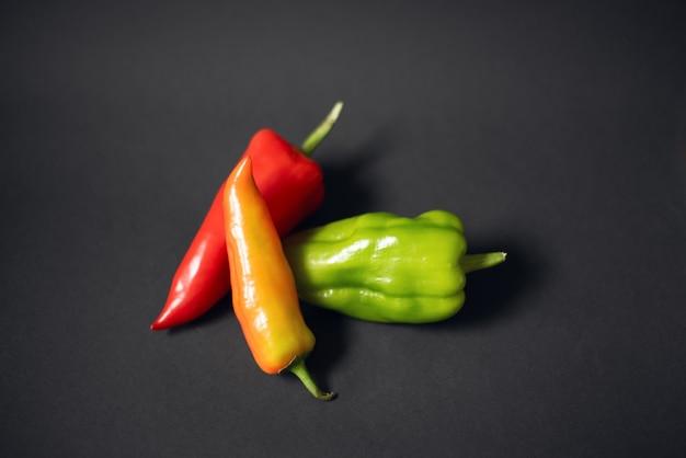 Tre peperoni di colore diverso su sfondo nero scuro