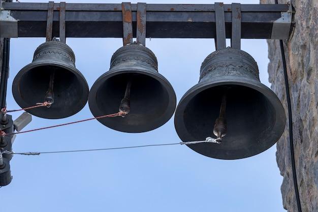 Tre campane sono appese al campanile della chiesa cristiana. foto di alta qualità