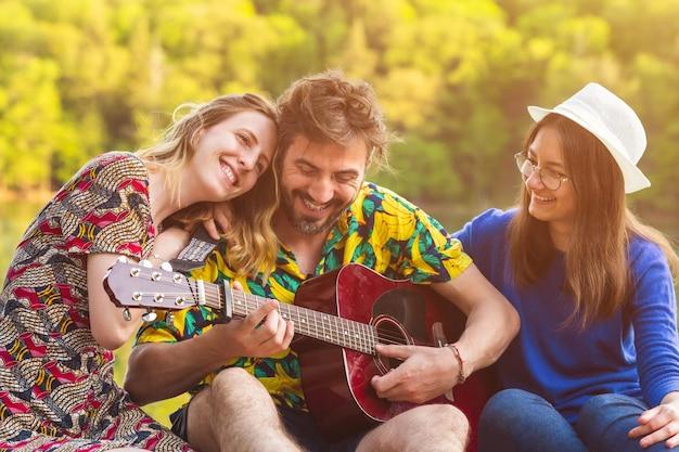 Tre migliori amici che suonano la chitarra insieme durante il viaggio di vacanza gruppo di amici felici che si divertono in riva al fiume lifestyle persone amicizia e musica