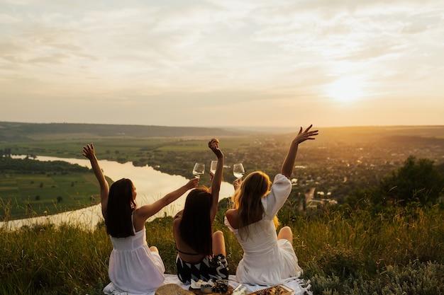 Tre migliori amiche che si divertono insieme in un picnic in montagna al tramonto.
