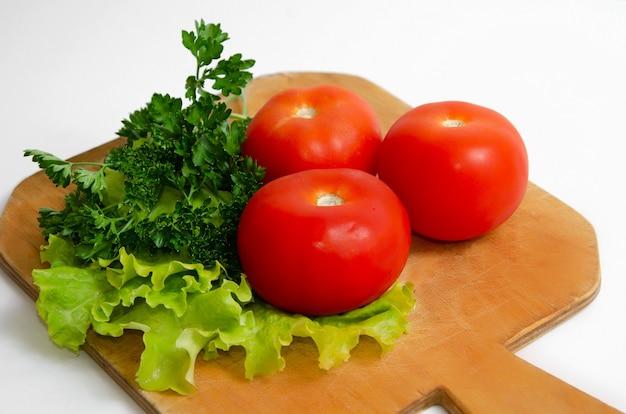 Tre grandi pomodori verdi tavola di legno concetto di cibo sano vegetarianismo, dieta keto, dieta paleo.