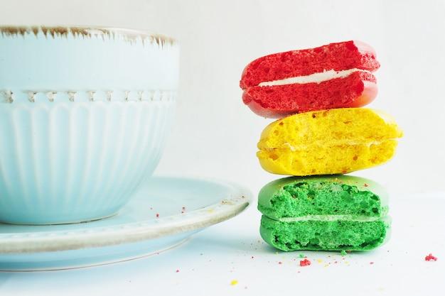 Tre torte di amaretto pungenti di colori gialli e verdi rossi in una pila vicino a una tazza blu su un tavolo bianco.