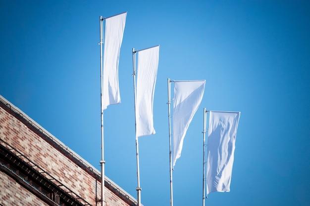 Tre bandiere bianche vuote sui pennoni contro il cielo blu nuvoloso con prospettiva, mockup di bandiera aziendale per logo, testo o simbolo dell'annuncio, modello di bandiera di identità aziendale con spazio di copia
