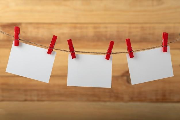 Tre carte di carta bianca vuote appese con mollette sul piolo di corda su fondo di legno. copia spazio.