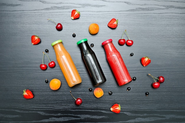 Tre bottiglie di succo e frutta. fondo in legno nero. concetto di cibo
