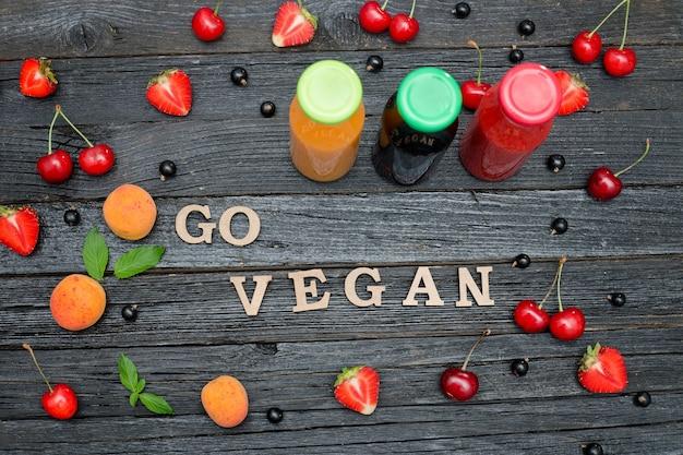 Tre bottiglie con succo, frutta e scritta go vegan. superficie in legno nero. concetto di cibo