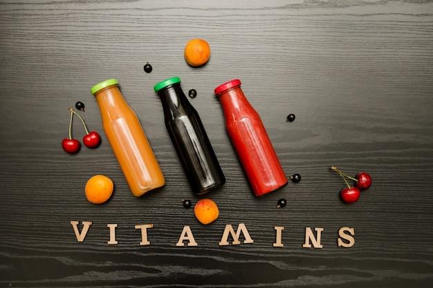 Tre bottiglie con succo, frutta e vitamine per iscrizioni su una superficie di legno nera, concetto di cibo food