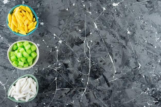 Tre ciotole piene di caramelle dolci colorate su una superficie di marmo