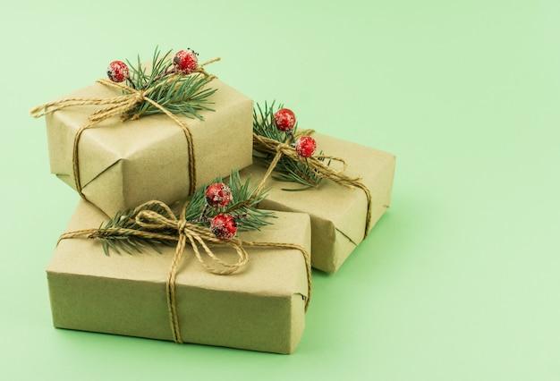 Tre scatole di regali in carta artigianale con decorazioni di rami di abete e bacche su sfondo verde.