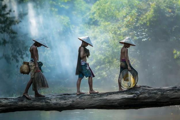 Tre ragazzi che pescano nel fiume, ragazzi in un cappello di paglia che tiene attrezzi da pesca, vietnam,