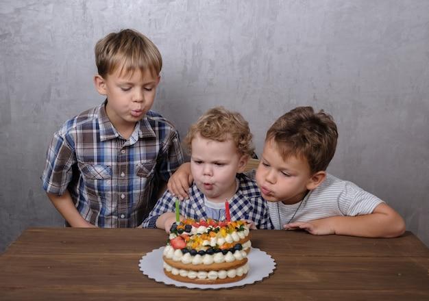 Tre fratelli spengono le candeline sulla torta di compleanno sotto forma del numero due in occasione del compleanno
