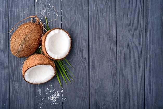 Noce di cocco marrone tre sul bordo di legno anziano