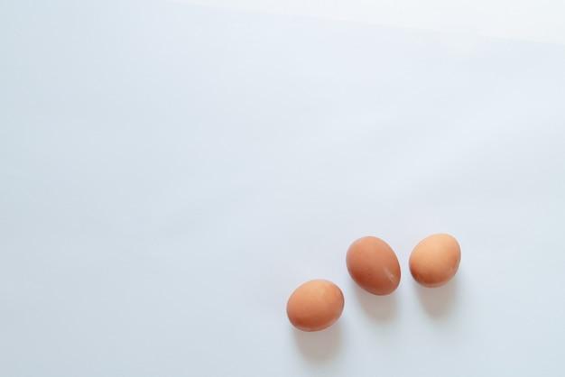 Tre uova marroni su sfondo bianco