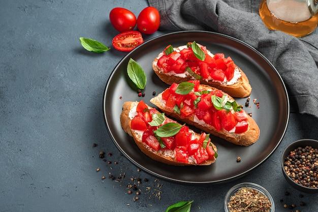 Tre bruschette con pomodori, basilico e formaggio su un piatto nero. uno spuntino tradizionale italiano. vista laterale.