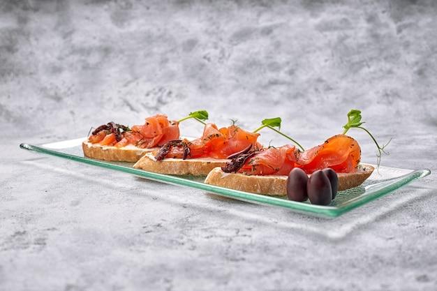 Tre bruschette con trota, salmone, crema di formaggio e microgreen su una lastra di vetro
