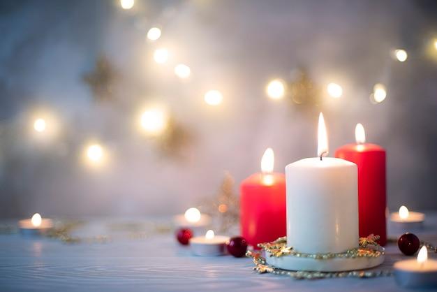 Tre candele accese e ghirlanda di natale su sfondo blu, primo piano