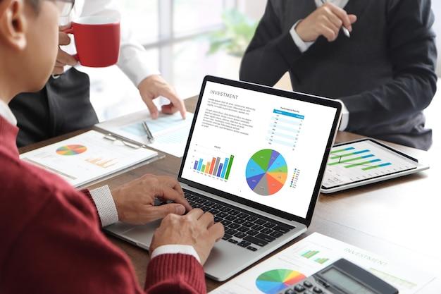 Tre uomini d'affari in una riunione in ufficio utilizzando un computer portatile o notebook mentre discutono di investimenti aziendali o rivedono i rendiconti finanziari.