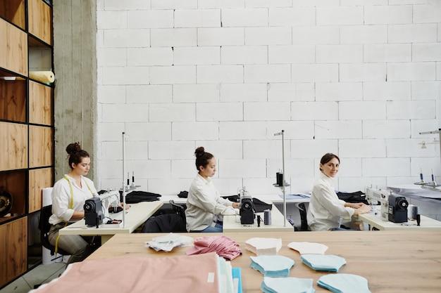 Tre designer femminili impegnate di articoli di cucito di moda per la nuova collezione sesonal mentre sedute in fila dai posti di lavoro in officina
