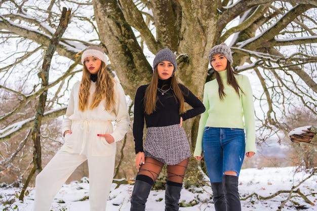 Tre amici caucasici che godono della neve in inverno sotto un albero