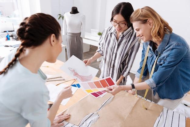 Tre donne allegre e affascinanti in piedi intorno al tavolo, tenendo in mano schemi di colori e uno schizzo e cercando di capire la migliore opzione di colore per un vestito di nuova concezione