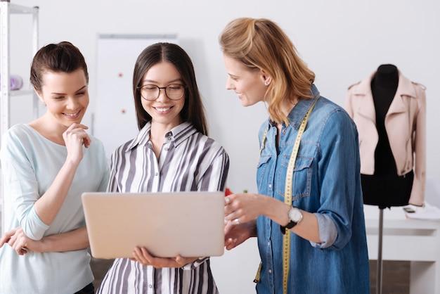 Tre giovani sarti affascinanti leggono un feedback sul loro lavoro e sorridono, mentre uno di loro tiene in mano un laptop e lo mostra ai colleghi