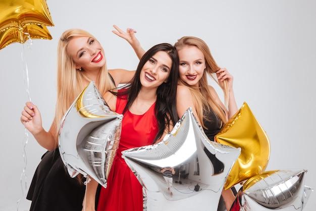 Tre belle giovani donne allegre con palloncini a forma di stella che si divertono insieme su sfondo bianco