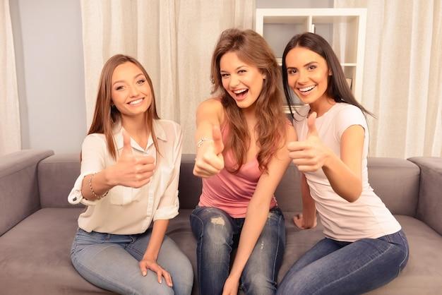 Tre amiche allegre che si siedono sul divano e mostrano un pollice in alto