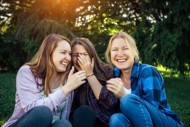 Tre ragazze allegre sussurrano e si divertono contro il fogliame verde nel parco.