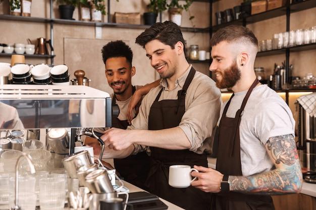 Tre allegri baristi maschi in piedi al bancone della caffetteria al chiuso Foto Premium