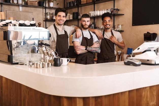 Tre allegri baristi maschi in piedi al bancone della caffetteria al chiuso