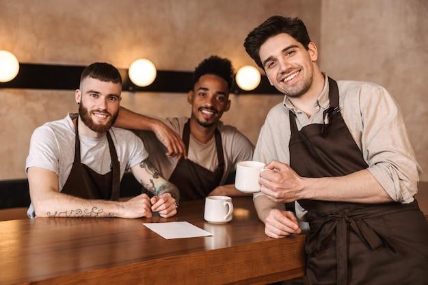 Tre baristi uomini allegri al bar, che bevono caffè durante la pausa