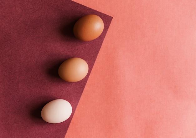 Tre uova di gallina vengono deposte su carta di colori naturali. la trama della carta e dell'uovo è beige.