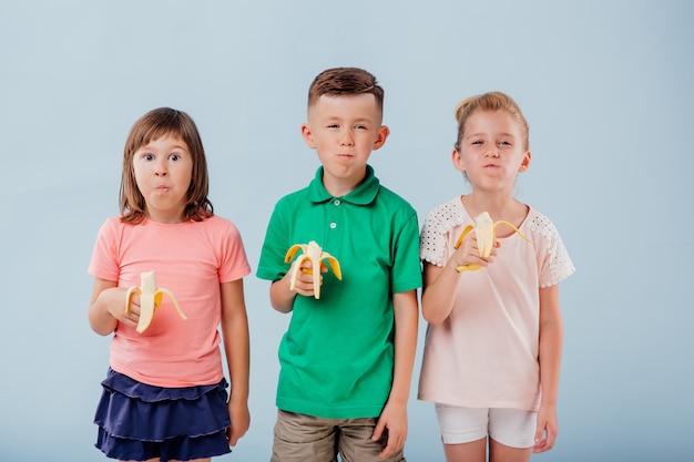 Tre bambini che mangiano banane fresche