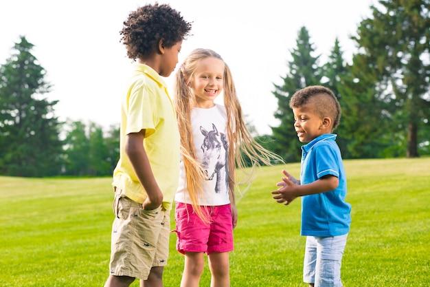 Tre bambini hanno una conversazione emozionante nella radura soleggiata
