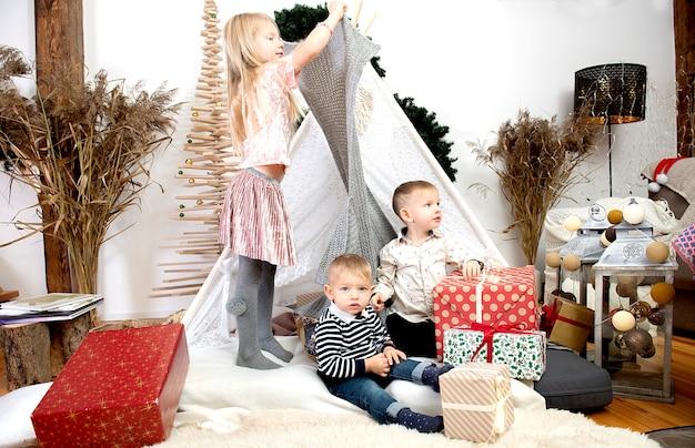 Tre bambini bambini che giocano tra scatole regalo di natale in una casa decorata.buon natale e buone feste!