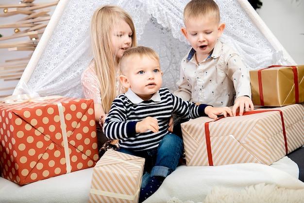 Tre bambini bambini seduti tra scatole regalo di natale in una casa decorata.buon natale e buone feste!