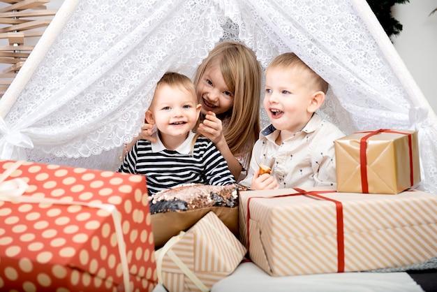 Tre bambini sorridono tra scatole regalo di natale in una casa decorata.buon natale e buone feste!