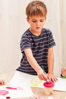Tre bambini imparano a dipingere con pennello e acquerelli su carta all'asilo
